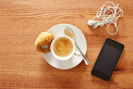croissants: Having coffee and croissants with smartphone and headphones