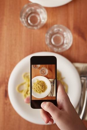 point and shoot: Manos que toman la foto de la comida de pasta italiana con el tel�fono inteligente