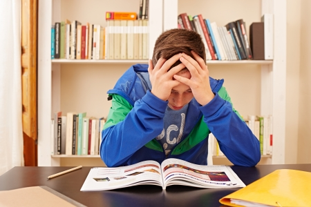 preoccupied: Male teenager worried doing homework in a desk