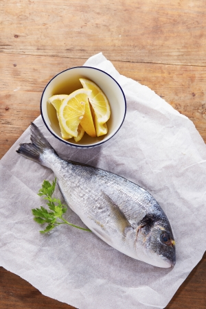 gilt head: Raw gilt head bream on white paper with lemon and parsley
