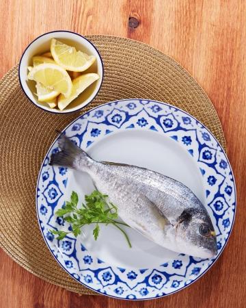 gilt head: Raw gilt head bream on a dish with lemon and parsley