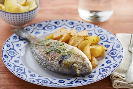 gilt head: Fried gilt head bream with potatoes in a restaurant table