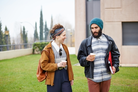 Hipster couple talking and drinking coffee to go at university campus photo