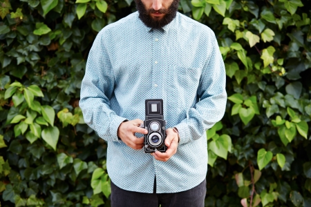 Young bearded hipster taking photo with TLR camera outdoor photo