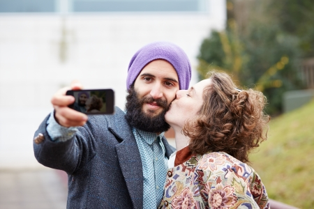 Couple taking a photograph of themselves kissing with a smartphone outdoors photo
