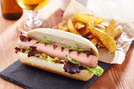 Gourmet hot dog on slate board with rustic fries photo
