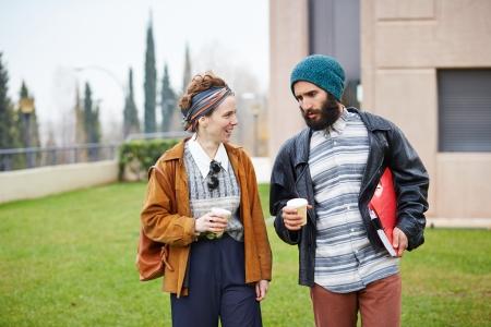 caf� � emporter: couple hippie de parler et de boire du caf� pour aller sur le campus de l'universit� Banque d'images