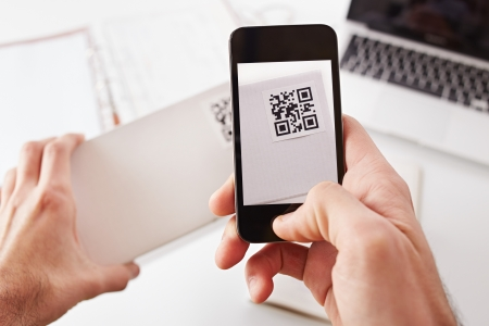 Smartphone taking photo of QR code on a white box photo