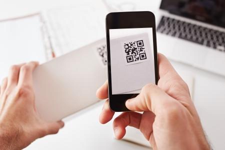 bar code reader: Smartphone toma la foto de c�digo QR en una caja blanca