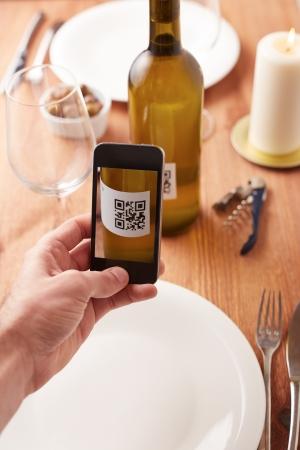 internet movil: Smartphone toma la foto de c�digo QR en una botella de vino Foto de archivo