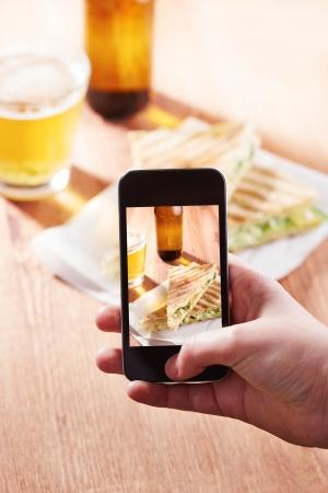 Smartphone taking photo of feta cheese sandwich on a restaurant