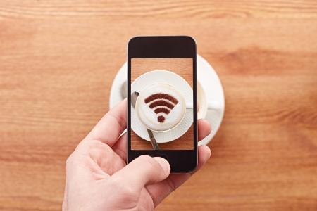 internet movil: Smartphone que toma la fotograf�a de la se�al wifi gratis en un caf� latte en un bar