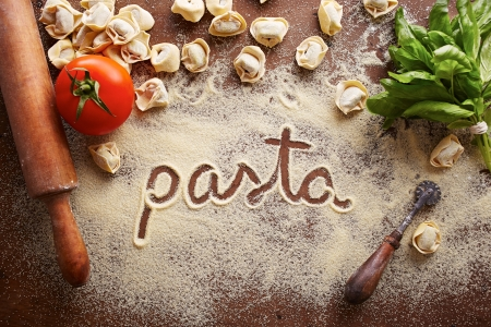 Pasta word written on table composition with ingredients photo