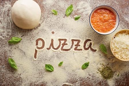 pizza: Pizza woord geschreven op tafel samenstelling met ingrediënten Stockfoto