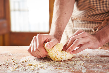 Bakers hands baking dough on wooden table photo