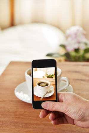capture the moment: Smartphone taking picture of coffee in a bar