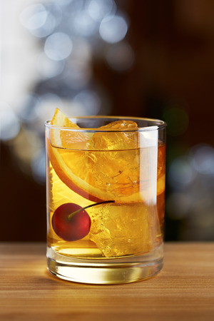 appealing: Old fashioned cocktail with a cherry on fancy background