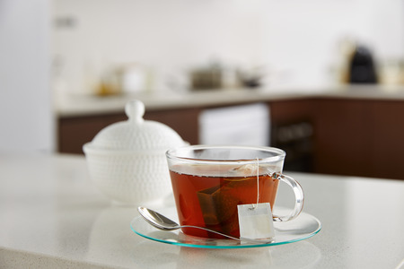 Glass cup of tea on kitchen counter photo