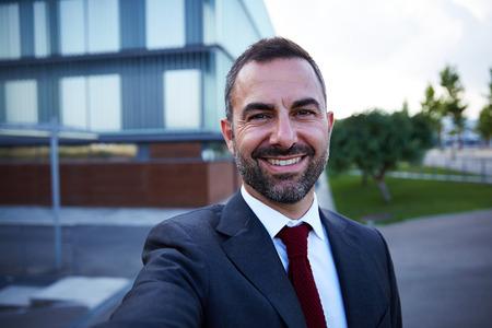 businessman in office: Businessman in a suit smiling selfie