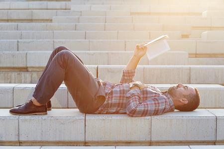 bel homme: Beau lecture d'affaires moderne se trouvant � l'ext�rieur sur des escaliers Banque d'images