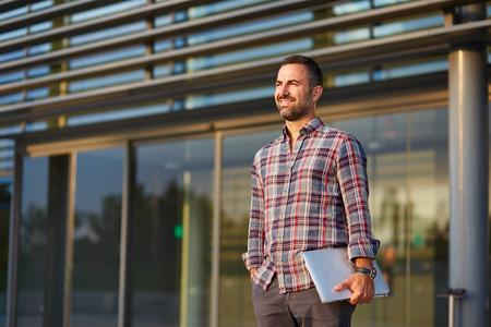 oficina trabajando: Hombre de negocios moderno hermoso que se coloca fuera de la oficina