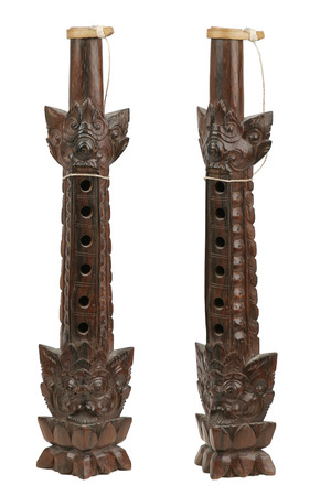 Balinese flute, elaborately carved form wood, 2 angles, separated on a white background.