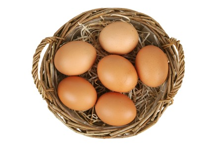 Wicker basket with six brown eggs. Top view. Isolated on white. path included.