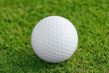 Golf ball on the green. Shallow DOF, focus on ball.