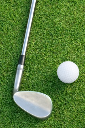 Golf ball and club on the green. Shallow DOF, focus on ball and head of club. Stock Photo