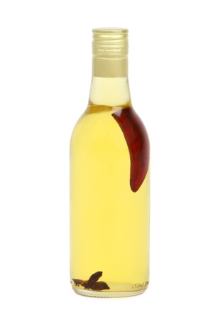 Bottle of vegetable cooking oil with a pepper and anise in it. Isolated on white. Stock Photo
