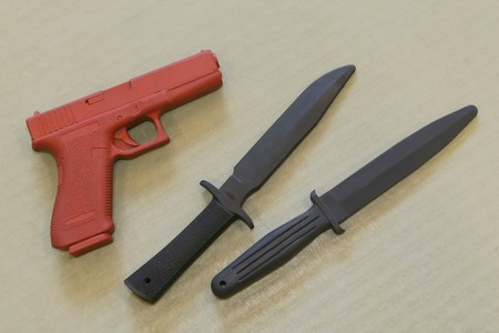 sidearm: Self defence practice weapons on a typical martial art mat background.
