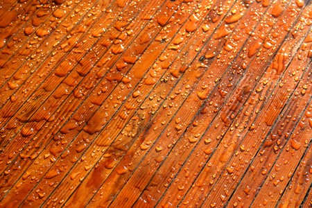 Waterdrops on red brown wood reflecting in the sun.