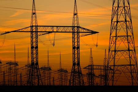power distribution: high voltage towers at sunset