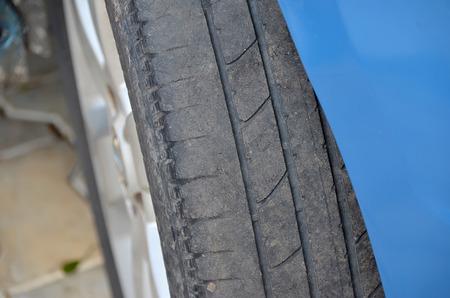 summer tire: worn tire of a blue car detail photo