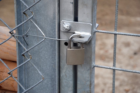metal gate: metal padlock locking new metal gate and fence