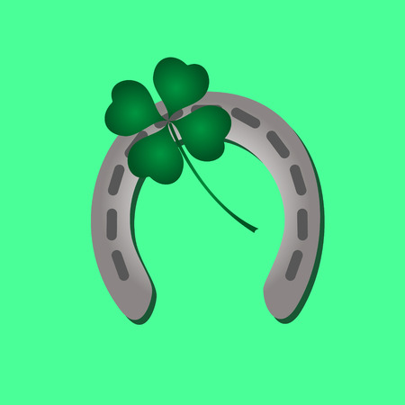 silver metal horseshoe and green cloverleaf