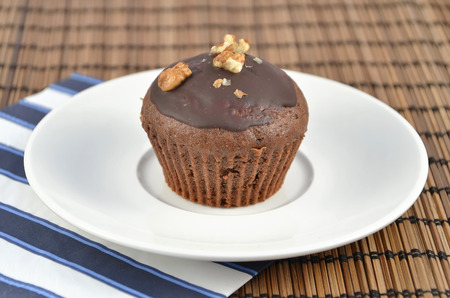 one chocolate brown muffins on white plate with color napkin best dessert Stock Photo