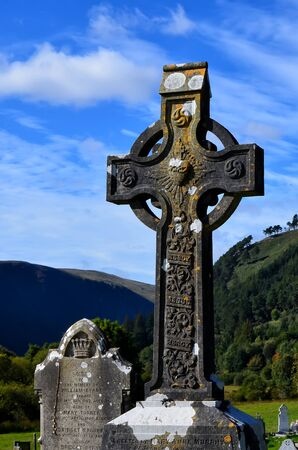 old Ireland celtic stone cross in cemetery at blue sky