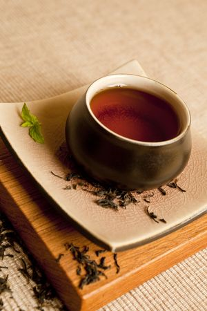 Black tea still life in a beautifull ceramic pot with mit and dry tea leaves. photo