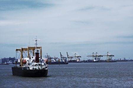 Transport ship on sea, cranes and harbor in background photo