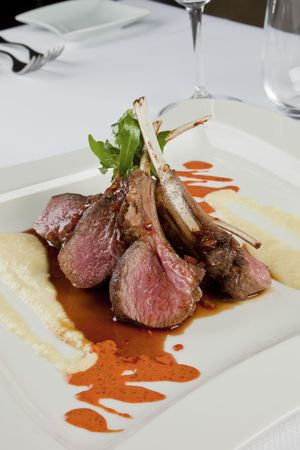 fine cuisine: Exquisite lamb ribs delicious served on a white plate.