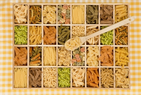 kind: Different noodle sorts in wooden box with wooden spoon. Stock Photo