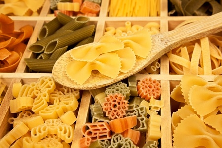 Different pasta sorts arranged in wooden box with wooden spoon. photo