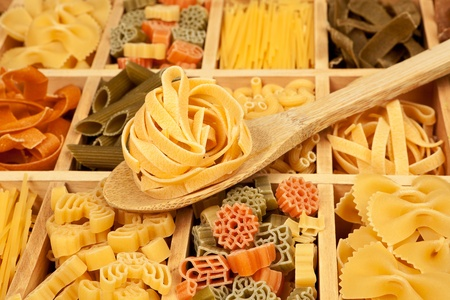 Pasta variation - different pasta sorts in wooden box with wooden spoon. photo