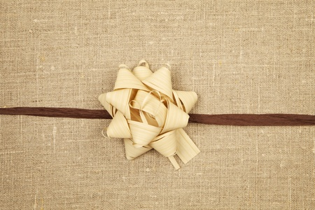 Ecology concept. Wrapped gift with ribbon on brown background with clipping path.