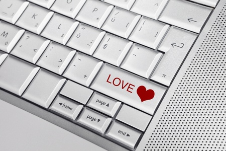 long distance: Silver keyboard with heart icon and LOVE text on keys. Internet love concept.