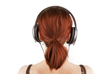 listening back: Attractive female with red hair and a tail with headphones isolated on white. Back view.