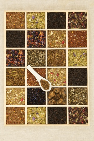 Different tea sorts in wooden box. Dry tea leaf collection. Top view. photo