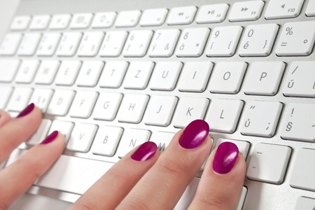 Female's hand with red nails touching a white metal keyboard. Stock Photo - 9174897