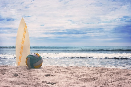 Surfboard and ball on empty beach against blue sky and turquoise ocean. Summer. Stock Photo